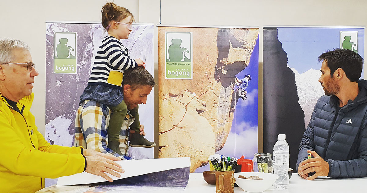 Tommy Caldwell signing posters at Bogong Equipment with his daughter on his shoulders